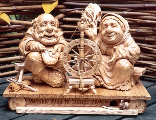 wood carving couple spinning a wheel art works by mfirsanov