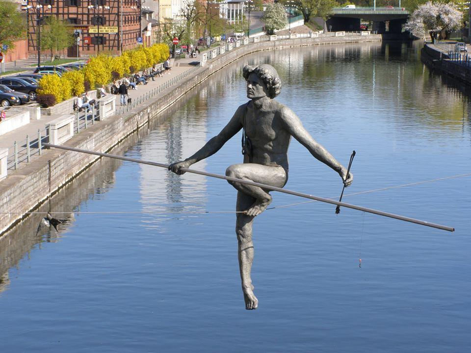 man balancing sculptures